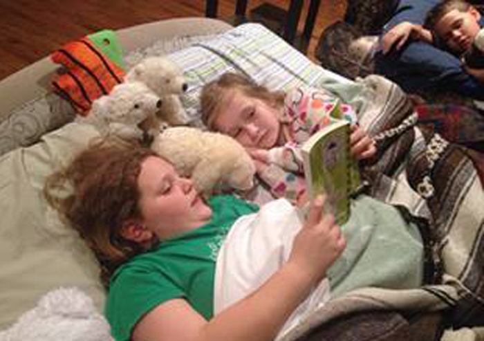 Girl reading in bed with her best read-aloud books