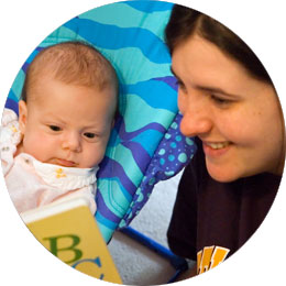 Mom reading Dr. Seuss ABC book to newborn in bouncy seat