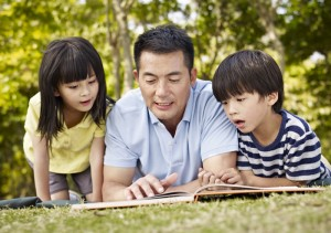 Father_reading_to_kids_at_the_park_700x493