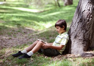 boy_reading_book_under_a_tree