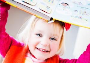 preschool_girl_playing_book_on_head_700x493
