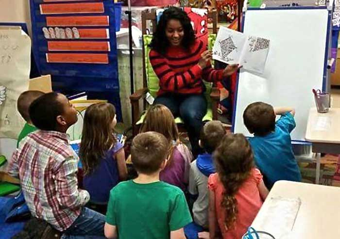 Sabrina Grandhi reading to a an elementary school classroom