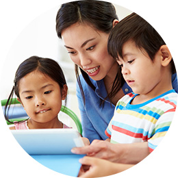 girl and boy looking at tablet with mom