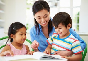 girl and boy reading with mom