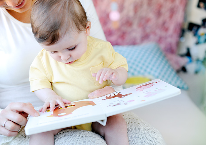Baby looking at a book with mom