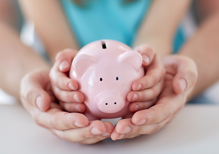A parent and child hold a piggy bank - helping parents with the question of whether and how to give kids an allowance.