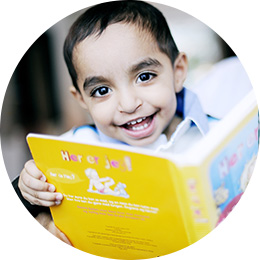 2-year-old smiling with a book