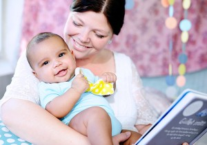 Baby cuddling with mom and a book