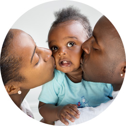 Baby being kissed by parents