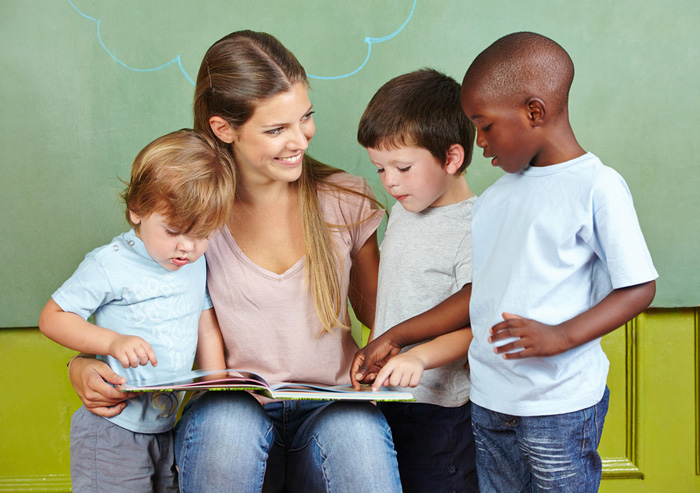 Three little boys enjoying a favorite first-grade book with a teacher
