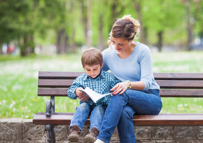 Mom and son reading a favorite kindergarten book on a park bench