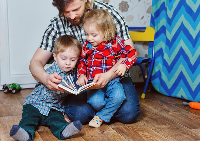 Father reading his favorite preschool books to his son and daughter.