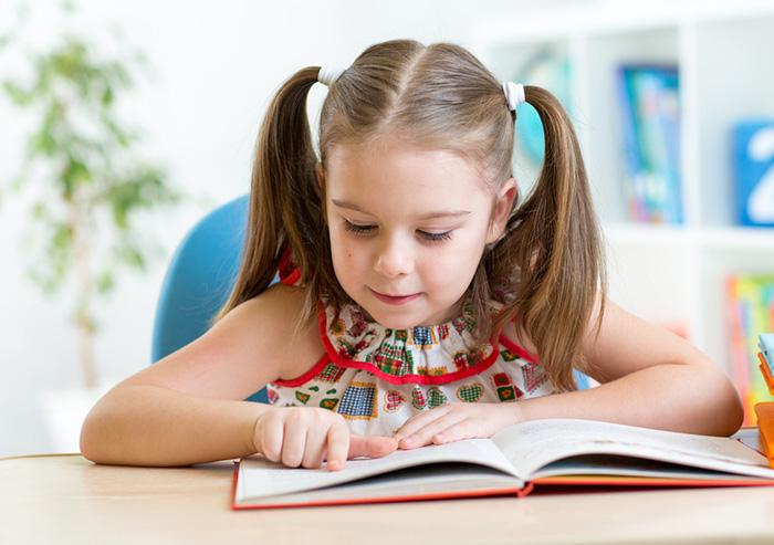 An little girl enjoying a favorite third-grade book on her own