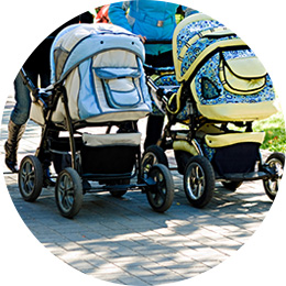 two moms walking babies in strollers