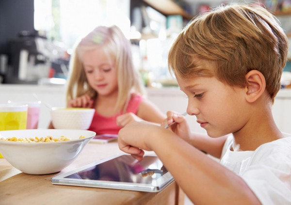 Boy with tablet at breakfast table