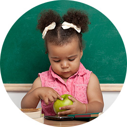 girl practicing her vocabulary with an apple