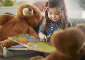 Girl reading aloud to her teddy bears