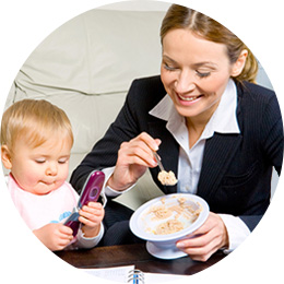Working mother feeding her baby before going to work