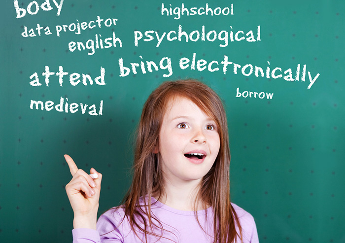 Girl pointing to words on a blackboard