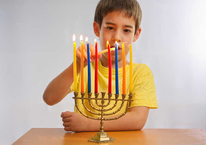 boy lighting a menorah