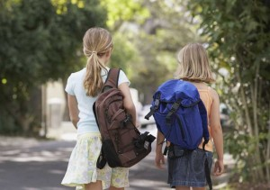 School aged girls walking to school with backpacks
