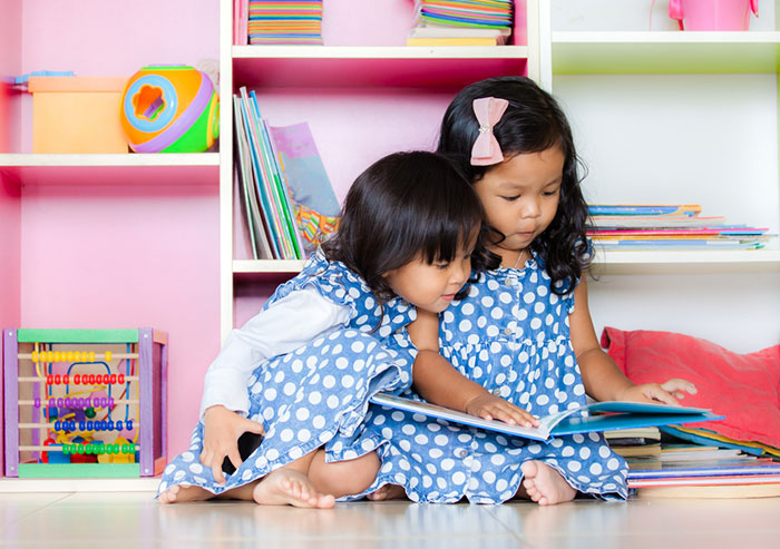 Sisters reading  books at home